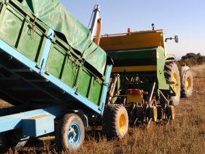 Remolque de agricultor genuino cargando sembradora para labores de agricultura